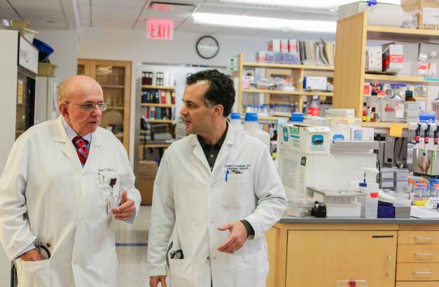 Dr. Silver talks with a colleague in the lab.